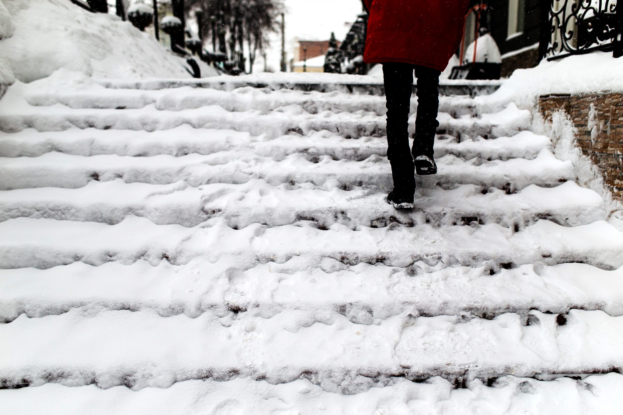 woman walking up snow covered stairs